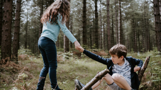 Girl helping boy up from the ground in the woods - photo credit @anniespratt