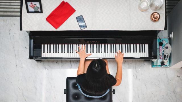 Woman playing piano, photo taken from overhead, photo credit @jon_chng