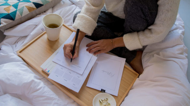 Woman writing or studying on a table in bed, with coffee preparing to find a co-op job in Canada. Photo credit @paicooficial
