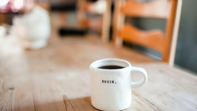 "white coffee mug on a table with the with the word ""Begin"" on it"